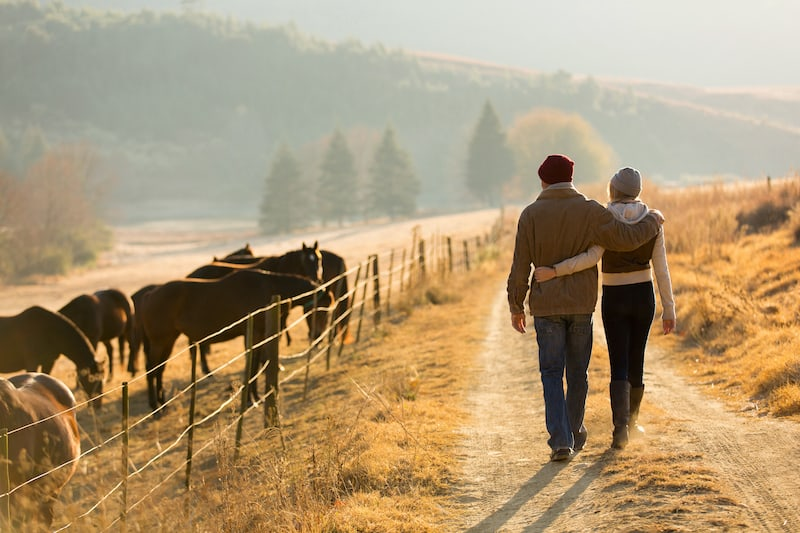 a couple walking down the road of their hobby farm in BC